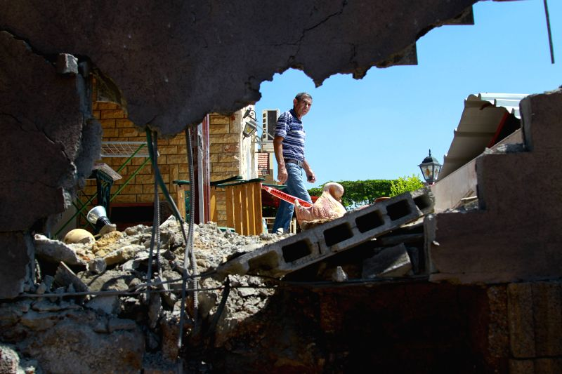 SDEROT (ISRAEL), July 3, 2014 An Israeli man inspects the damage of a house following a projectile attack by militants from Gaza in Sderot, Israel, on July 3, 2014. Earlier on Thursday, ..