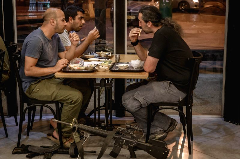 Israeli reserve soldiers enjoy their meals at a local restaurant in Sderot, south Israel bordering the Gaza Strip, on July 26, 2014. Israeli security cabinet has ...