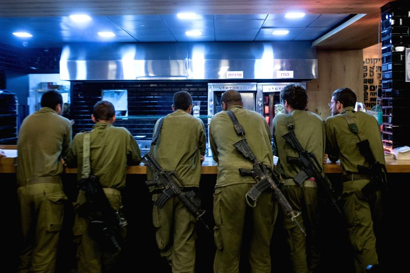 Israeli reserve soldiers wait for their meals at a local restaurant in Sderot, south Israel bordering the Gaza Strip, on July 26, 2014. Israeli security cabinet has .