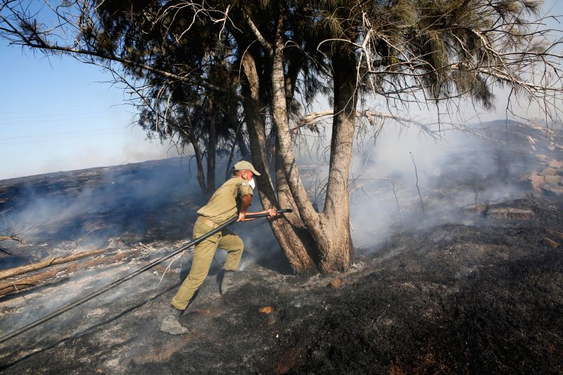 SDEROT, July 31, 2018 - An Israeli firefighter attempts to extinguish a fire caused by inflammable materials in a forest field outside Sderot, Israel, near the border between Israel and Gaza Strip, ...