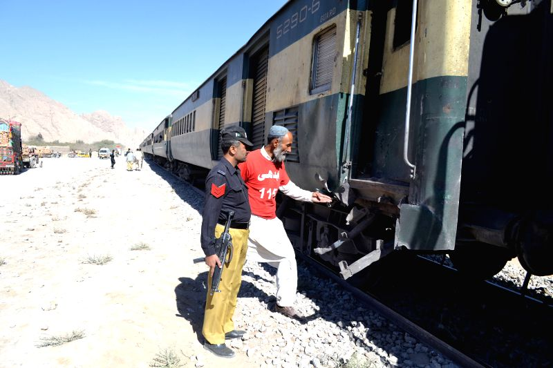 Security officials examine a passenger train at the blast site in Mastung district of Balochistan, Pakistan, Nov. 1, 2015. At least four people were killed and 10 ...