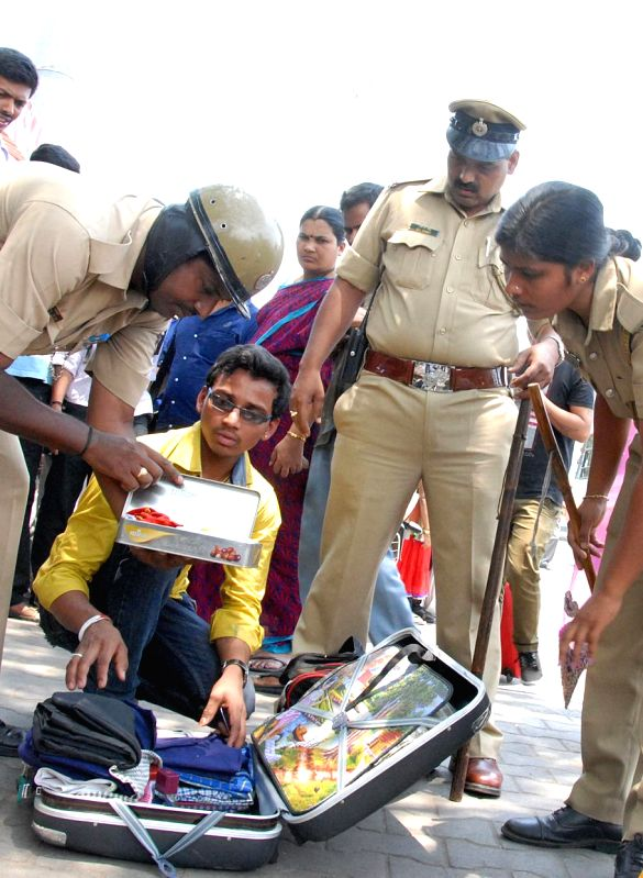 Security personnel check baggage of a passenger at Bangalore railway station in light of the two bomb blasts that took place in the coaches of a Guwahati-Bangalore train, minutes after it chugged ...