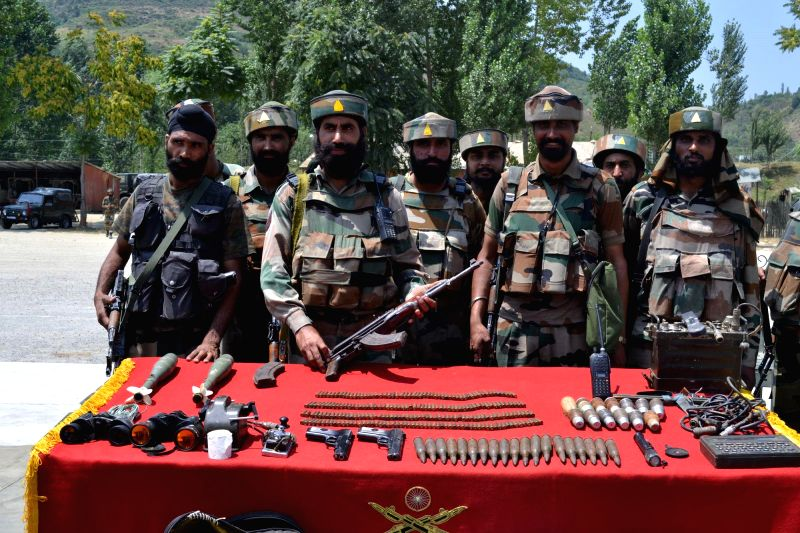 Security personnel display arms, ammunition and other devices recovered during a raid on a militant hideout in Baramulla on July 27, 2014.