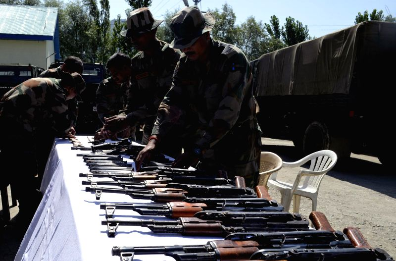 Security personnel display arms and ammunition recovered from a militant hide-out in Bandipora district of Jammu and Kashmir on Aug 21, 2014.