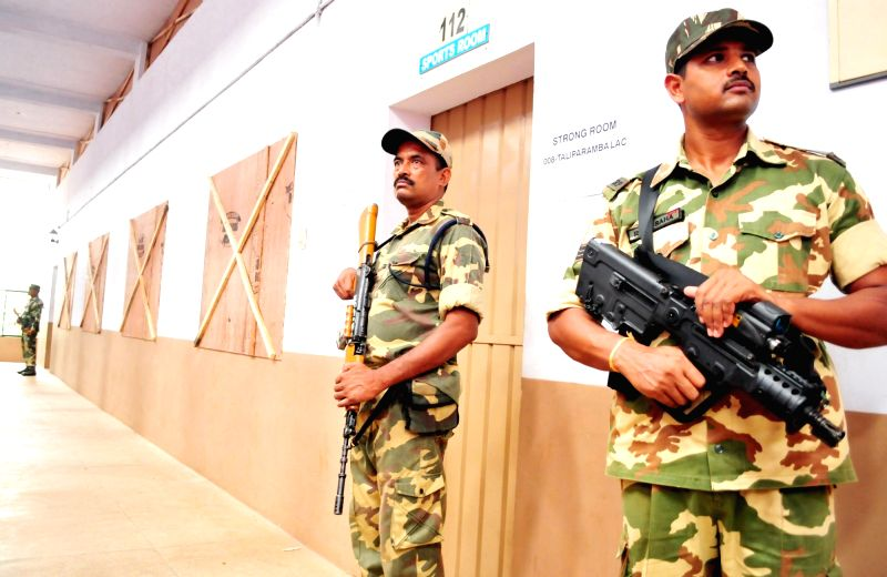 Security personnel in large numbers deployed outside a strong room where EVMs are stored after Kerala Assembly election at the Chinmaya Institute of Technology in Kannur, Kerala on May 17, ...