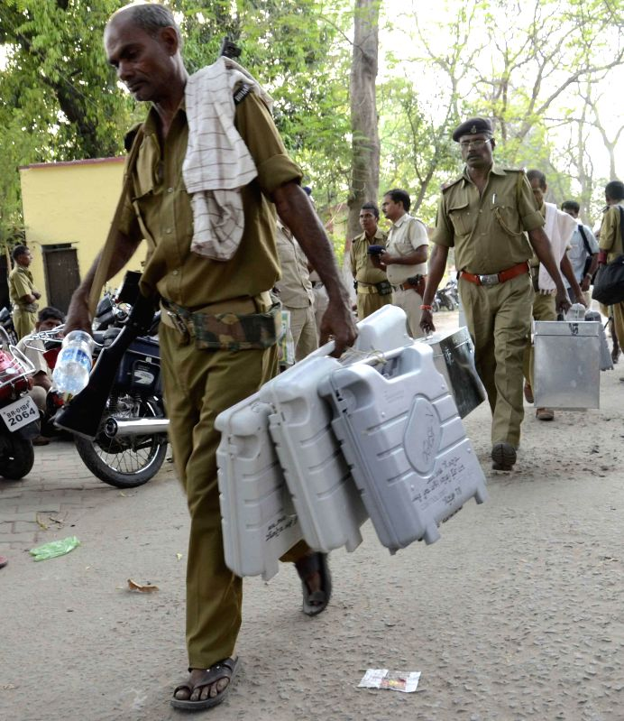 Security personnel leave for their respective polling booths with Electronic Voting Machines (EVMs) ahead of the 5th phase of 2014 Lok Sabha Elections from a polling station in Patna on April 16, ...