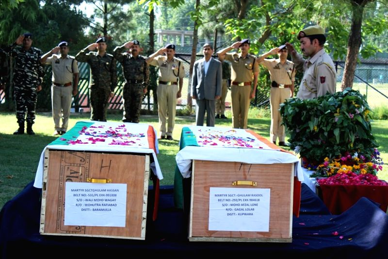 Security personnel pay tributes to the two policemen who were killed in a militant attack in Jammu and Kashmir's Pulwama district on June 12, 2018.