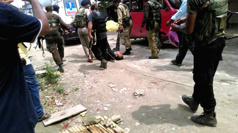 Security personnel take away body of a  man killed in Kokrajhar terror attack on Aug 5, 2016. At least 12 civilians were killed on Friday when militants in military fatigues opened random ...