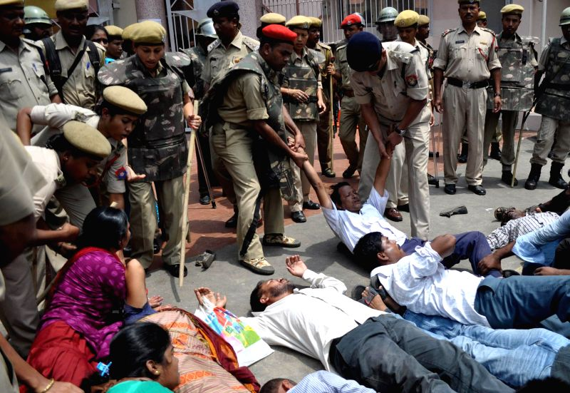 Security personnel take away KMSS activists demonstrating against against police after two people were killed in a police firing near Assam-Nagaland border in Golaghat district of Assam, in Guwahati .