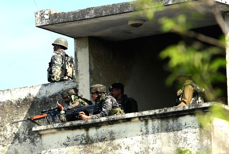 Security personnel take position during an encounter with militants who attacked a police station in Kathua district of the Jammu on March 20, 2015.