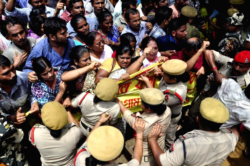 Security personnel try to stop activists of the Krishak Mukti Sangram Samity (KMSS) demonstration in front of Directorate of Health Services, Government of Assam, Hengrabari against government's ...