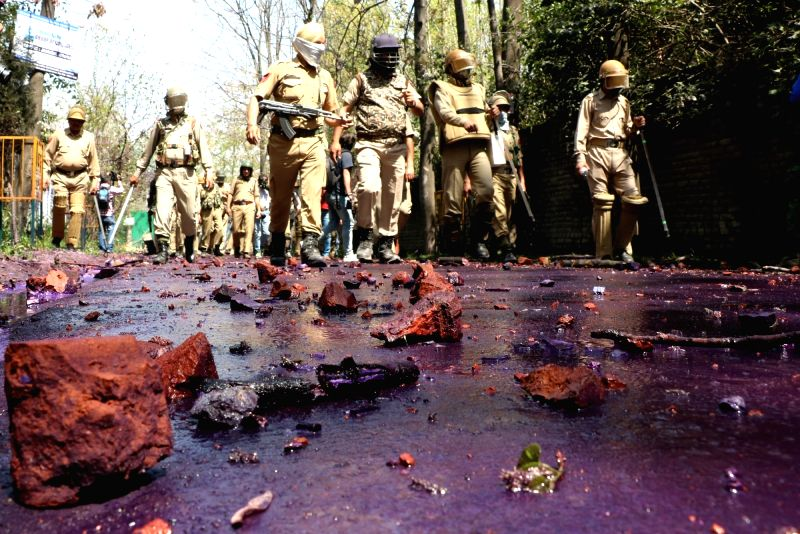 Security personnel walk on a stone strewn road after protesters pelted stones on them. (File Photo: IANS)