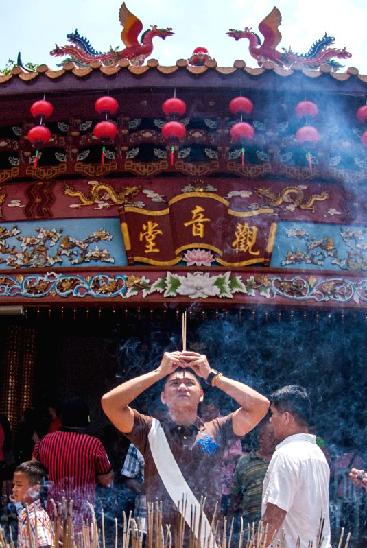A man burns incense to pray during Chinese traditional Spring Festival at a temple in a small town in the south of Selangor state, Malaysia, on Feb. 22, 2015. ...