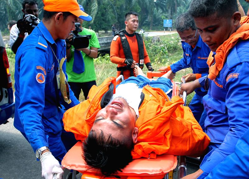 Rescuers transfer a survivor in Selangor, Malaysia, June 19, 2014. A boat carrying 97 people sank near Banting, Selangor of Malaysia early Wednesday. Eleven people