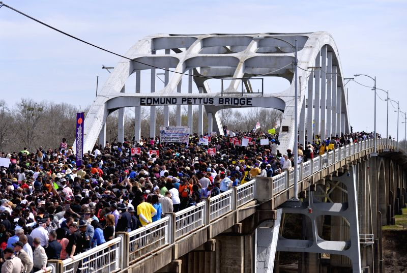 """Tens of thousands of people walk across the Edmund Pettus Bridge during the 50th anniversary in commemoration of """"Bloody Sunday"""" in Selma, Alabama, the ..."""