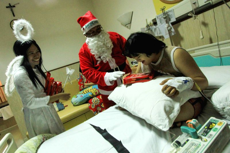 A man dressed as Santa Claus gives a patient presents for Christmas at St. Elisabeth hospital in Semarang, Indonesia, Dec. 25, 2014.