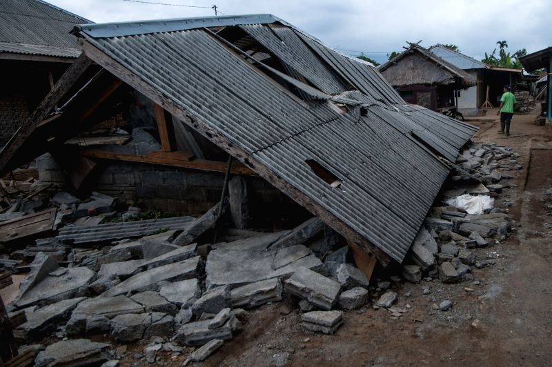 SEMBALUN (INDONESIA), July 31, 2018 A local resident passes a house that collapsed in the earthquake at Sajang village, East Lombok in Indonesia, July 31, 2018. A 6.4-magnitude quake ...