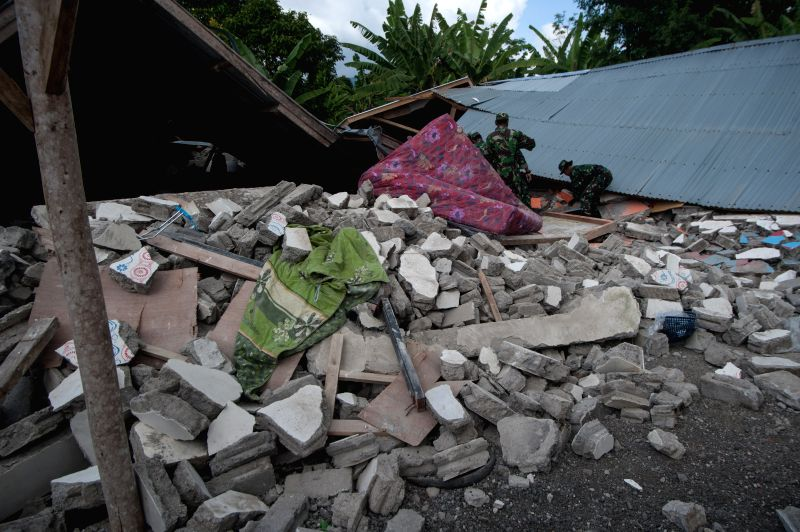 SEMBALUN (INDONESIA), July 31, 2018 Soldiers help a local resident to find useful items in the collapsed house at Sajang village, East Lombok in Indonesia, July 31, 2018. A 6.4-magnitude ...