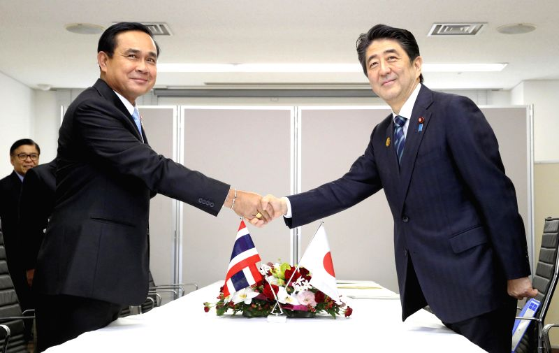 Japanese Prime Minister Shinzo Abe (R) shakes hands with Thai Prime Minister Prayuth Chan-ocha during their talks in Sendai, Japan on March 14, 2015. (Xinhua ...