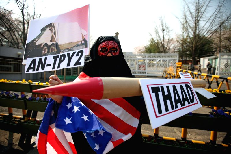 A protester holds placards during a rally against U.S. Defense Secretary Ashton Carter's visit and the deployment of Terminal High-Altitude Area Defense (THAAD), a ...
