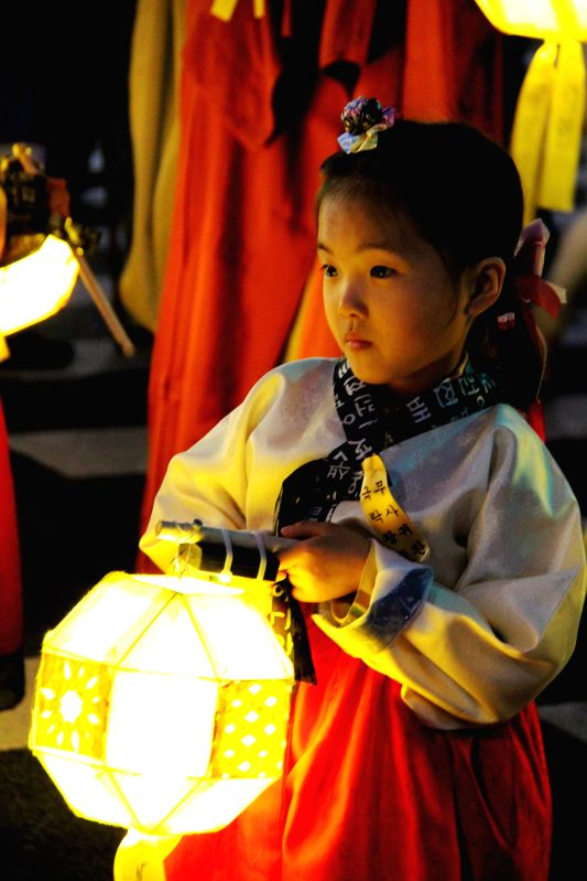 A girl takes part in a parade to give blessing for those deceased or missing persons of the capsized passenger ship Sewol during the Lotus Lantern Festival for ...