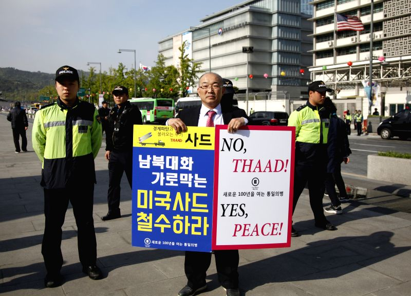 SEOUL, April 28, 2017 - A protester holds posters during a demonstration against the Terminal High Altitude Area Defense (THAAD) in Seoul, South Korea, on April 27, 2017. South Korean people and ...
