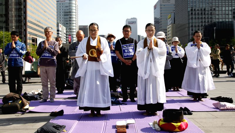 SEOUL, April 28, 2017 - Protesters pray for peace during a demonstration against the Terminal High Altitude Area Defense (THAAD) in Seoul, South Korea, on April 27, 2017. South Korean people and ...
