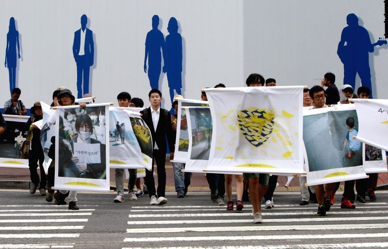 . South Korean photographers and artists march through downtown district in memory of the victims of the ferry Sewol disaster in Seoul, South Korea, Aug. 11, 2014. ...