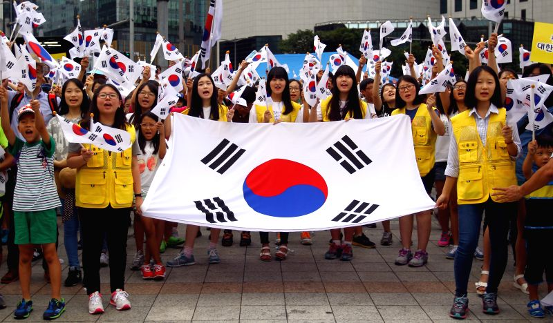 Local residents take part in an activity marking the 69th anniversary of the Korean peninsula's liberation from Japan's 35-year colonial rule in Seoul, South Korea, ..