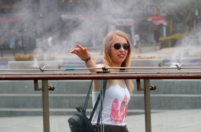 SEOUL, Aug. 3, 2018 - A foreign visitor cools herself in a misting fountain at the Gwanghwamun square during a hot summer day in Seoul, South Korea, Aug. 3, 2018.