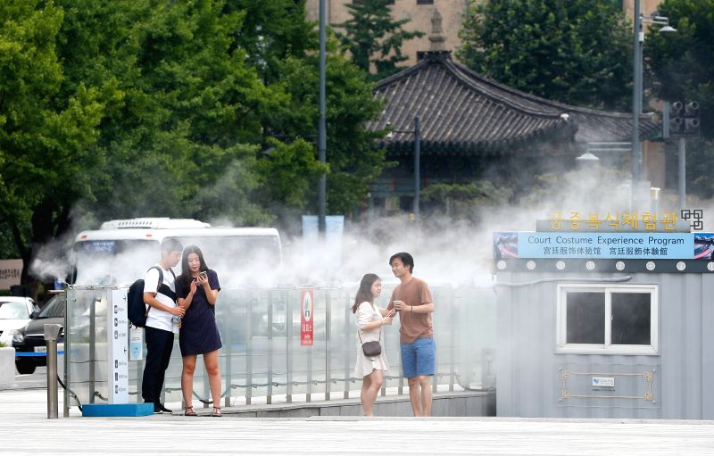 SEOUL, Aug. 3, 2018 - People cool themselves in a misting fountain at the Gwanghwamun square during a hot summer day in Seoul, South Korea, Aug. 3, 2018.