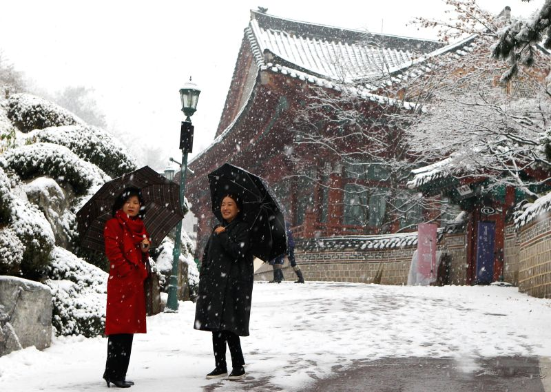 Tourists enjoy a snowfall in Seoul, South Korea, on Dec. 15, 2014. The snowfall started on the afternoon of Monday in Seoul and would last for several days, according