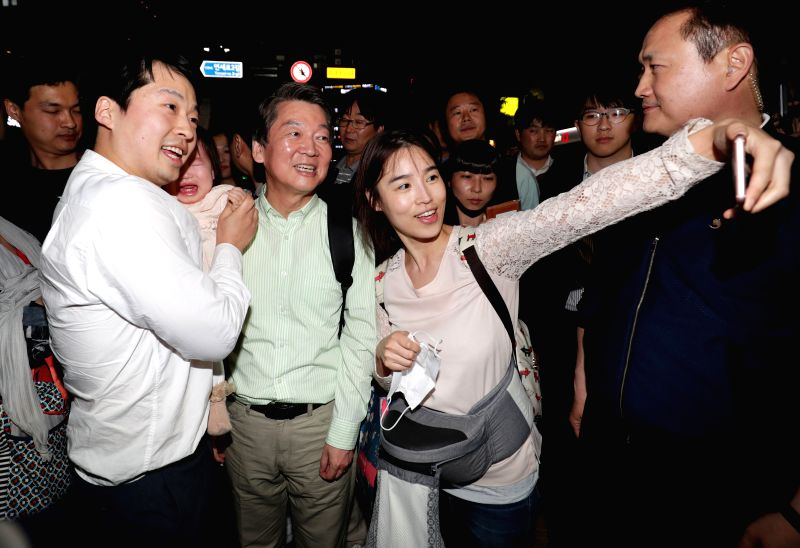 SEOUL, May 8, 2017 - South Korean presidential candidate Ahn Cheol-soo (C, front) of the People's Party has photos taken with citizens during a campaign in Seoul, South Korea, on May 7, 2017. A ...