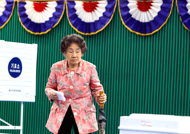 SEOUL, May 9, 2017 - A woman prepares to cast her ballot in the presidential election at a polling station in Seoul May 9, 2017. South Korea on Tuesday held the 19th presidential election.