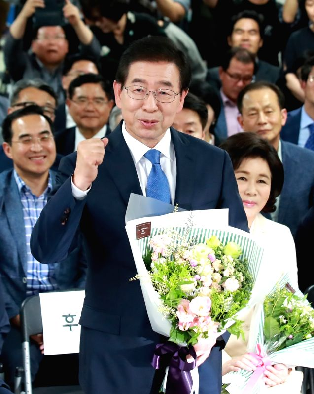 Seoul Mayor Park Won-soon pumps his fist at his campaign office in Seoul on June 13, 2018, as he was certain to win the mayoral race in the local and parliamentary by-elections.