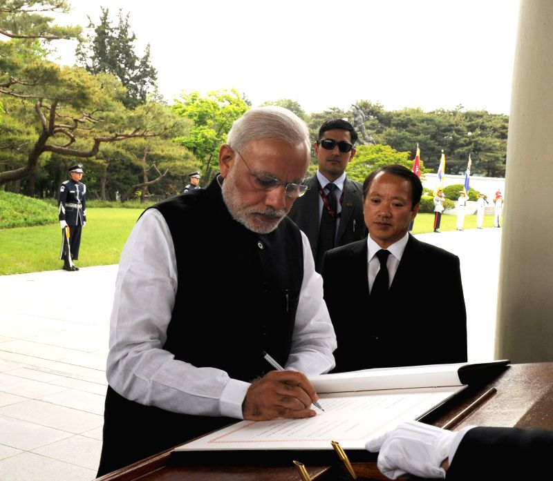 Prime Minister Narendra Modi signing the visitor`s book during the Wreath laying ceremony, in Seoul National Cemetery, South Korea on May 18, 2015. - Narendra Modi