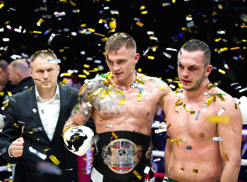 Sergej Maslobojev (C) from Lithuania poses for photo after beating Robert Dorin from Romania in a KOK world belt 93kg title match in Vilnius, Lithuania, Nov. 14, ...