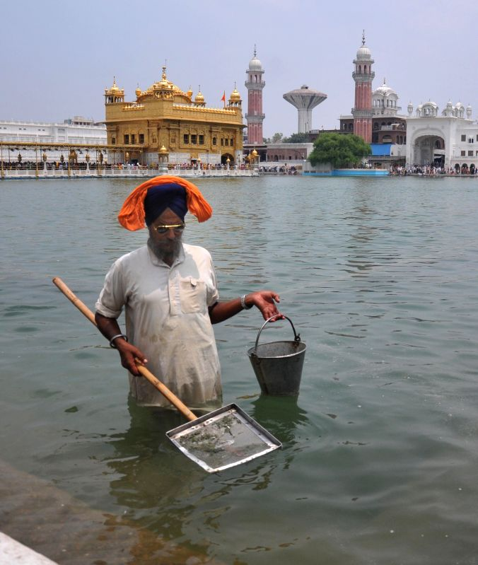 Sewadar at Golden Temple cleaning the sarovar (holy tank) on July 26, 2014.