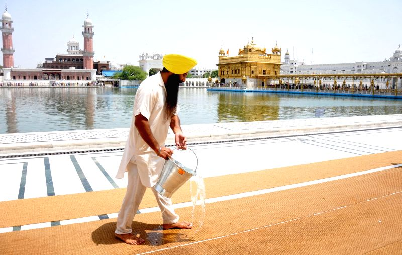 Sewadar at Golden Temple pouring water on carpet laid for Parikarma to protect devotees' feet from hot floor as tempearture rises in Amritsar on June 17, 2014.
