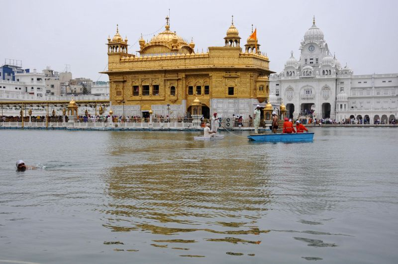 Sewadars clean the holy sarovar (holy tank) aboard a boat at Golden Temple in Amritsar on July 2, 2014.