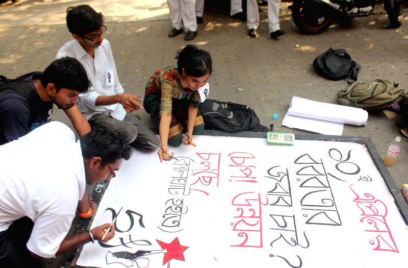 SFI activists write posters to protest against West Bengal Government at Presidency College in Kolkata on April 10, 2014.