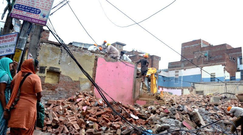 SGPC personnel demolish shops at Chowk Baba Saheb near Golden Temple in Amritsar on June 29, 2014.