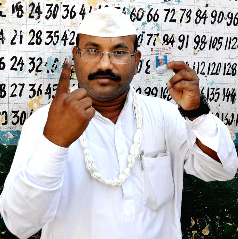 Sham Lal Gandhi who is contesting 2014 Lok Sabha Election as an independent candidate from Amritsar parliamentary constituency shows his fore finger marked with phosphorous ink after casting his vote