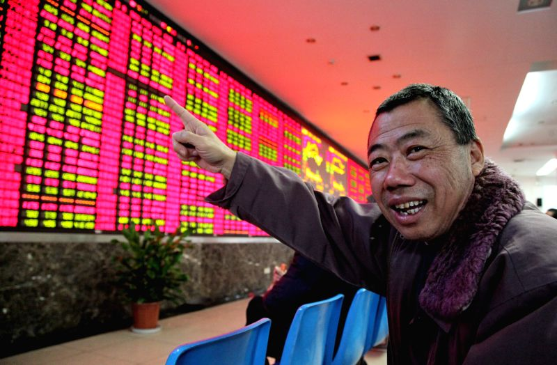 An invester points at an electronic billboard displaying share prices in a stock trading venue in east China's Shanghai, Dec. 3, 2014. China's stocks saw a rise on Wednesday with the ...