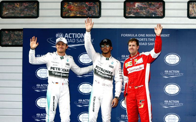 Mercedes driver Lewis Hamilton(C) of Britain waves with teammate Nico Rosberg(L) of Germany and Ferrari driver Sebastian Vettel of Germany after getting pole in ...