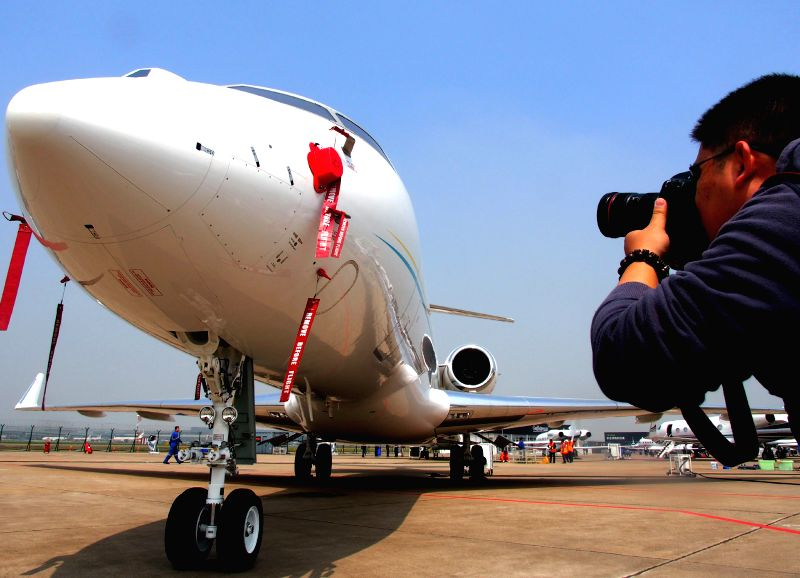 A visitor takes photos of an airplane prior to the Asian Business Aviation Conference and Exhibition (ABACE) in Shanghai, east China, April 14, 2014. A total of ..