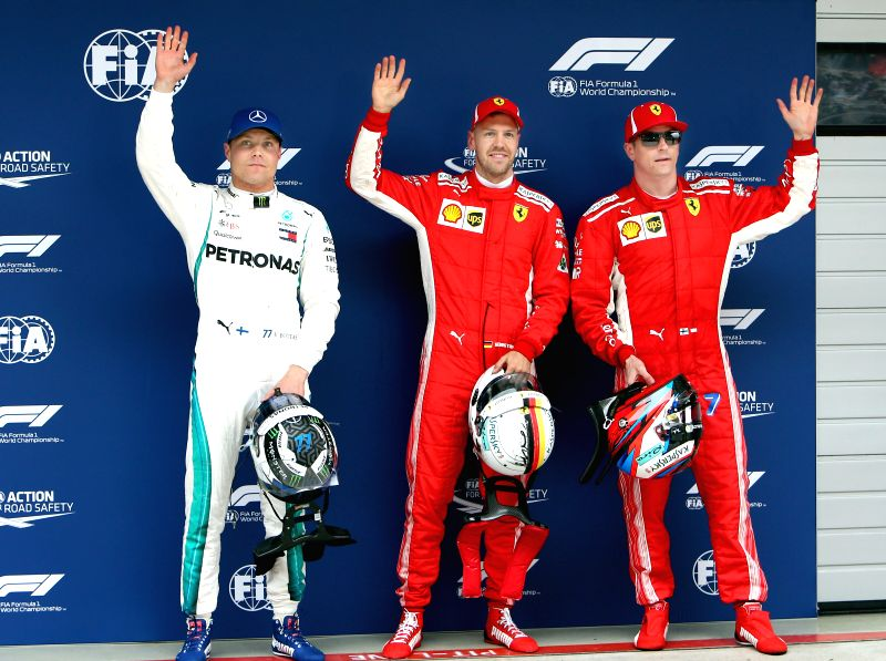 SHANGHAI, April 14, 2018 - First-placed Ferrari's driver Sebastian Vettel (C) of Germany, second-placed Ferrari's driver Kimi Raikkonen (R) and third-placed Mercedes' Valtteri Bottas wave to ...