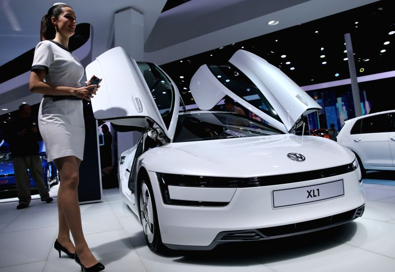A staff member of the auto show walks by a vehicle of Volkswagen during the Auto Shanghai 2015, east China's Shanghai, April 20, 2015. A total of 1,343 complete ...