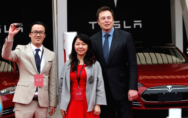 Elon Musk (1st R), CEO of American electric car maker Tesla Motors, poses with the first group of owners of Tesla vehicles of China in Shanghai, east China, April