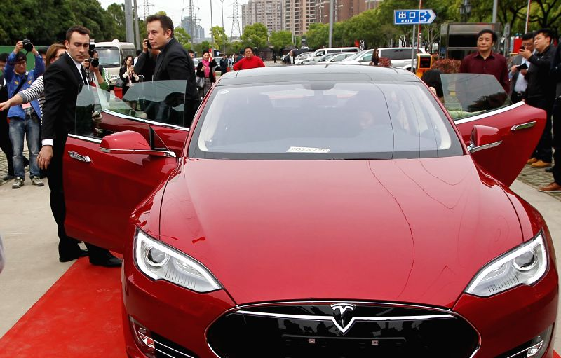 Elon Musk (2nd L), CEO of American electric car maker Tesla Motors, gets off a Tesla vehicle in Shanghai, east China, April 23, 2014. The first supercharger ...